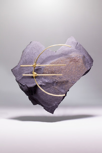 Euro symbol made of metallic wire on heart shape stone against white backgroundの写真素材 [FYI04323495]