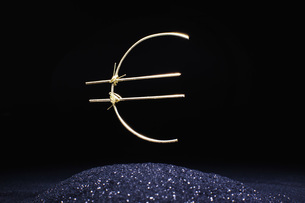 Euro symbol made of metallic wire in mid-air over shiny sand against black backgroundの写真素材 [FYI04323496]
