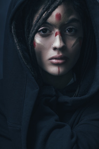 Portrait of beautiful woman with face paint wearing black jacketの写真素材 [FYI04323507]