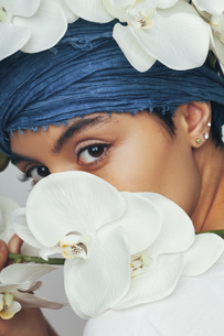 Portrait of woman hiding behind fresh white orchidsの写真素材 [FYI04323510]