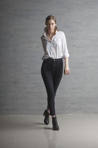 Portrait of confident beautiful fashion model walking against wallの写真素材 [FYI04323516]