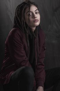 Portrait of beautiful fashion model wearing maroon jacket against black wallの写真素材 [FYI04323530]