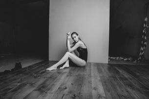 Portrait of fashion model sitting hardwood floor against wallの写真素材 [FYI04323533]