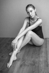 Portrait of confident woman wearing leotard sitting on hardwood floor against wallの写真素材 [FYI04323543]