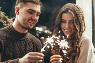 Smiling couple playing with sparklers during Christmas celebrationの写真素材 [FYI04323545]
