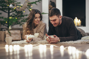 Smiling couple having coffee while lying on rug at home during Christmasの写真素材 [FYI04323546]