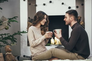 Smiling couple having coffee while sitting on rug at home during Christmasの写真素材 [FYI04323550]