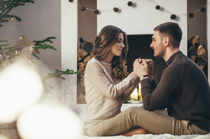 Romantic couple having coffee while sitting at home during Christmasの写真素材 [FYI04323551]