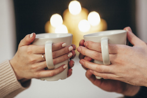 Cropped image of couple holding coffee cups against illuminated candles at homeの写真素材 [FYI04323552]