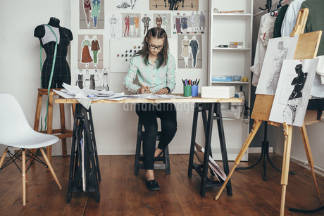 Beautiful female design professional working at workbench in studioの写真素材 [FYI04323553]