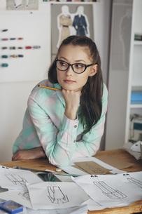 Thoughtful beautiful fashion designer looking away at workbench in studioの写真素材 [FYI04323558]