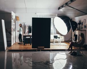 Female fashion designer and trainee with illuminated strobe lights at clothing studioの写真素材 [FYI04323560]