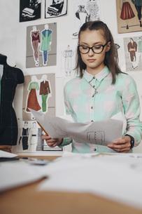 Beautiful fashion designer looking at sketches workbench in studioの写真素材 [FYI04323561]