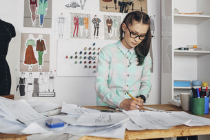 Beautiful fashion designer drawing sketch at workbench in studioの写真素材 [FYI04323562]