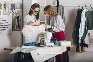 Trainee examining dress's fabric by designer holding coathanger at fashion studioの写真素材 [FYI04323566]