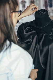 Rear view of fashion designer holding straight pins on dressmaker's model at studioの写真素材 [FYI04323567]