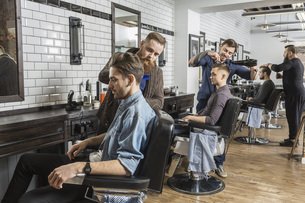 Hairdressers cutting male customer's hair in salonの写真素材 [FYI04323570]