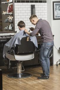 Barber cutting male customer's hair at salonの写真素材 [FYI04323572]