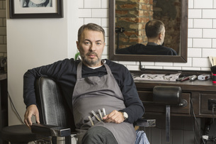 Portrait of mature barber sitting on chair at hair salonの写真素材 [FYI04323576]