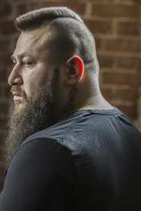 Close-up of male hairdresser with beard looking away at barber shopの写真素材 [FYI04323577]