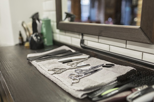 Close-up of various scissors and combs on napkin at hair salonの写真素材 [FYI04323588]