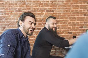 Cheerful barbers sitting against brick wall at hair salonの写真素材 [FYI04323589]