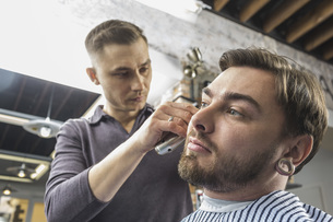 Low angle view of male hairdresser cutting young customer's hair at barber shopの写真素材 [FYI04323592]