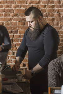 Male hairdresser mixing coffee while standing amidst coworkers against brick wall at barber shopの写真素材 [FYI04323593]