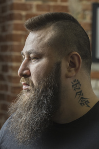 Close-up of male hairdresser with tattoo and beard looking away at barber shopの写真素材 [FYI04323597]