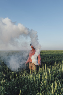 Man standing with distress flare emitting smoke on field against blue skyの写真素材 [FYI04323599]
