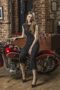 Portrait of beautiful smiling woman sitting on motorcycle by foosball tableの写真素材 [FYI04323604]