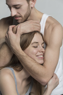 Man embracing smiling girlfriend against gray backgroundの写真素材 [FYI04323608]