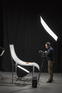 Full length of photographer photographing food in studio against black backgroundの写真素材 [FYI04323615]
