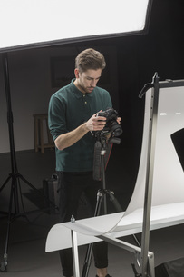 Confident photographer looking at backdrop while working in studioの写真素材 [FYI04323619]
