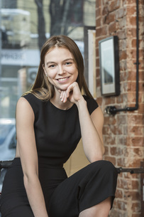 Portrait of smiling woman with hand on chin against brick wallの写真素材 [FYI04323626]