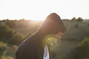 Side view of man wearing hooded jacket on field during sunny dayの写真素材 [FYI04323627]