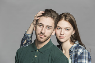 Portrait of young couple standing against gray backgroundの写真素材 [FYI04323628]
