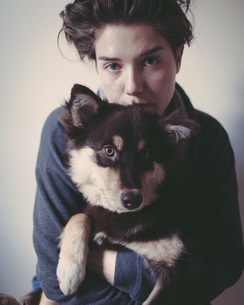 Portrait of confident woman embracing dog against gray backgroundの写真素材 [FYI04323632]