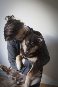 Affectionate young woman embracing dog against white backgroundの写真素材 [FYI04323642]
