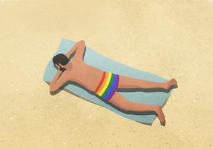 Man in rainbow swim trunks sunbathing on beachのイラスト素材 [FYI04323708]