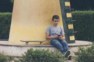 Teenage boy with skateboard using smart phoneの写真素材 [FYI04323749]