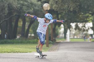 Boy playing, skateboarding in parkの写真素材 [FYI04323750]