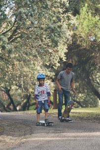 Brothers skateboarding in parkの写真素材 [FYI04323752]