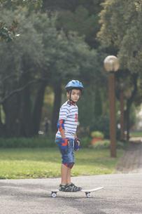 Portrait confident boy skateboarding in parkの写真素材 [FYI04323753]
