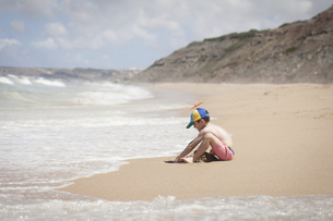 Boy playing in sand on sunny ocean beach, Lisboa, Lisbon, Portugalの写真素材 [FYI04323755]