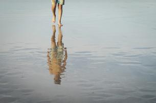 Teenage boy walking on wet sand beachの写真素材 [FYI04323759]