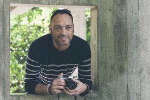 Portrait man with camera standing in garden windowの写真素材 [FYI04323760]