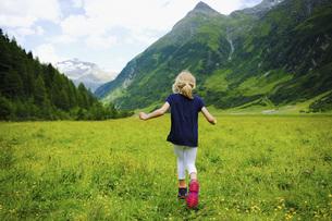 Carefree girl running in idyllic mountain valley, Innergschloess, Tyrol, Austriaの写真素材 [FYI04323768]