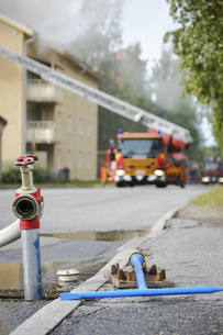 Fire truck tending to apartment fire with open fire hydrant in foregroundの写真素材 [FYI04323778]