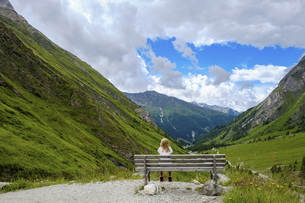 Girl sitting on bench looking at scenic mountain view, Innergschloess, Tyrol, Austriaの写真素材 [FYI04323783]